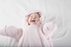 Laughing baby face in pink snowsuit. Six months age cute baby dressed up in pink fluffy winter snowsuit snug hoodie clothes lying on white sheet bed smiling Stock Images
