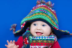 Laughing baby in funny knitted hat and scarf Stock Photography