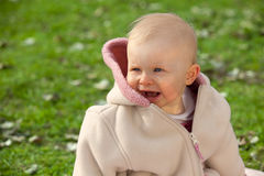 Laughing baby girl. A laughing one year old baby girl sitting in the meadow Stock Photography