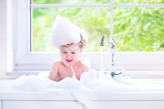 Laughing baby girl in big kitchen sink with foam Stock Photo