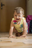 Laughing baby girl crawling on floor Royalty Free Stock Photos