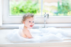 Laughing baby girl in kitchen sink next to window Royalty Free Stock Image
