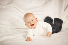 Laughing baby girl lying on a couch Royalty Free Stock Image