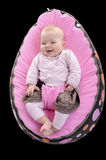 Laughing baby girl in lying in an egg shaped chair Stock Photo