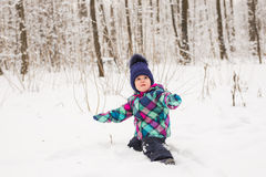 Laughing baby girl lying in the snow Royalty Free Stock Images