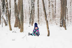 Laughing baby girl lying in the snow Royalty Free Stock Photos