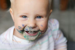 Laughing Baby Girl with Messy Paint on her Face. A happy, laughing one year old baby girl has a messy face covered in blue and purple paint Royalty Free Stock Image