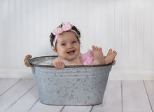 Laughing baby girl in metal bath tub. Laughing, mixed race baby girl in metal bath tub with bubbles stock photography