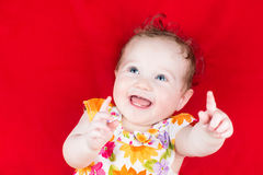Laughing baby girl playing on a red blanket Stock Photo
