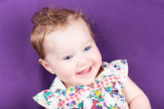 Laughing baby girl on a purple blanket Stock Photo