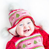 Laughing baby girl in a red dress with Christmas ornament. Happy laughing baby girl in a red dress with Christmas ornament Stock Photo