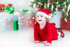 Laughing baby girl in a red dress and santa hat playing be Royalty Free Stock Images