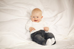 Laughing baby girl sitting on a couch Royalty Free Stock Photo