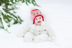 Laughing baby girl sitting under Christmas tree Royalty Free Stock Image