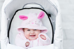 Laughing baby girl sitting in a white stroller in a bunny dress-up. Laughing happy baby girl sitting in a white stroller in a bunny dress-up stock photos