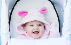 Laughing baby girl sitting in a white stroller in a bunny dress-up Royalty Free Stock Images