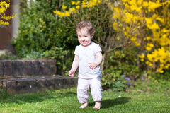 Laughing baby girl walking in the garden Royalty Free Stock Photos