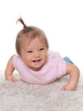 Laughing baby girl on the white carpet Royalty Free Stock Images