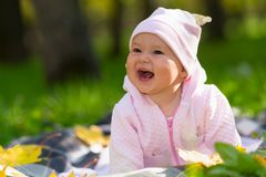 Laughing baby girl with a wide beaming smile. Laughing baby girl with a wide beaming smile playing on a blanket on the grass in an autumn park in a candid royalty free stock images