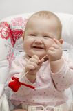 Laughing baby. A little laughing child sits on an arm-chair with a toy in hands stock photos