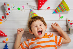 Laughing baby lying on the wooden floor with carnival party hat. Stock Photo