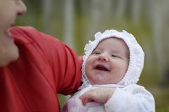 New Born Baby Smiling. Portrait of a beautiful baby laughing and laying on the hands of mothers. Stock Image