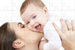 Laughing baby playing with mother puzzle Stock Image
