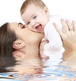 Laughing baby playing with mother in water Royalty Free Stock Photos