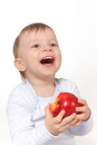 Laughing baby with red apple Stock Image