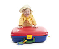 Laughing baby with red and blue suitcase, on white Royalty Free Stock Photos