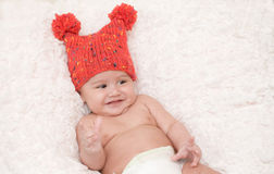 Laughing baby in red cap. A sweet, precious baby of three months of age is smiling.  He is on a white blanket and is wearing a red knitted cap with two pom poms Stock Photos