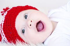The laughing baby in red knitted hat Royalty Free Stock Photo