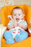 Laughing baby sitting on babies chair age of 6 month Stock Photos
