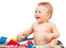 Laughing baby sitting in clothes. On white background stock photos