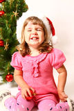 Laughing baby sitting near Christmas tree  Stock Image