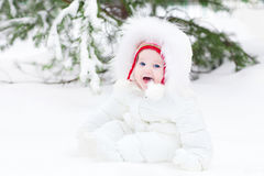Laughing baby sitting in snow under a Christmas tree Stock Photos