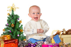 Laughing baby surrounded by Christmas gifts Stock Photo