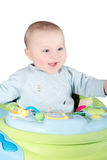 Laughing baby in walker. A baby in walker on isolated background Stock Image