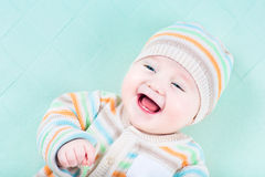 Laughing baby wearing warm knited jacket and hat Stock Images