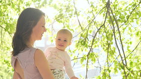 Laughing babygirl smile with mum at green back yard slowmotion stock footage