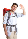 Laughing backpacker greeting at camera Stock Photo