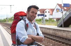 Laughing backpacker at railway station Royalty Free Stock Photo