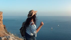 Laughing backpacker woman jumping dancing and having positive emotion admiring amazing seascape. From mountain. Happy travel female enjoying summer vacation at stock footage