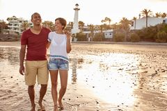 Laughing barefoot couple on the beach. Laughing barefoot adult couple walking along the beach with their arms around each other and hands interlocked in bright Royalty Free Stock Photography