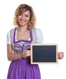 Laughing bavarian woman with curly blond hair and chalk board Stock Photos