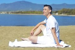 Laughing beach guy in white shorts and shirt. Entrepreneur enjoys staying on the beach. Man on beach lying in sand looking to side. Smiling happy. Young male Royalty Free Stock Image