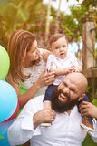 Laughing beard father with family. Holding his son on shoulders in garden Stock Image