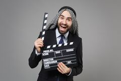 Laughing bearded arabian muslim businessman in keffiyeh kafiya ring igal agal suit isolated on gray background