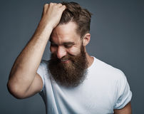 Laughing bearded man holding hair and laughing Royalty Free Stock Photography