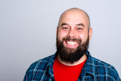 Laughing, bearded man in red and checkered shirt Stock Image